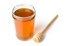 Jar of honey with a honey dipper Stock Photography