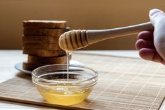 Jar of Honey with Honey Dipper with Toast Bread In the Background royalty free stock photo
