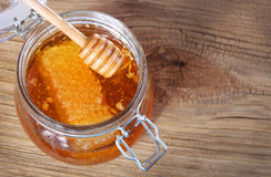 Jar of honey with honeycomb and dipper on wooden background Royalty Free Stock Photos