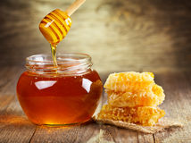 Jar of honey with honeycomb. On wooden table