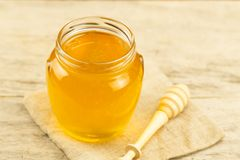 Jar of honey on jute fabric with drizzler on wooden background Stock Photo