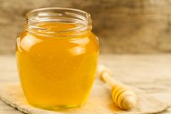 Jar of honey on jute fabric with drizzler on wooden background Stock Images