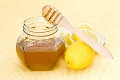 Jar of honey, lemon and wooden drizzler Stock Photography