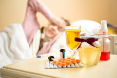 Jar with honey and medicines lying on table next to sick girl be Stock Photography