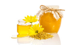 The jar of honey near a pile of pollen and flower Royalty Free Stock Images