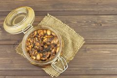 Jar of honey and nuts. Sweet treat for snacking. Pickled walnuts in honey. Royalty Free Stock Photography