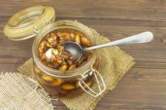 Jar of honey and nuts. Sweet treat for snacking. Pickled walnuts in honey. Royalty Free Stock Photo