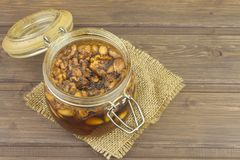 Jar of honey and nuts. Sweet treat for snacking. Pickled walnuts in honey. Stock Photography