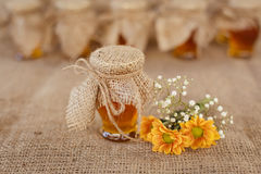 Jar with honey and orange flowers Royalty Free Stock Photos