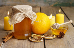 Jar of honey, oranges and candles on wooden table Stock Photo