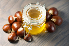 Jar of honey with organic chestnuts on a wooden table Stock Photography