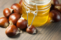 Jar of honey with organic chestnuts on a wooden table Royalty Free Stock Photos
