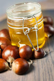 Jar of honey with organic chestnuts on a wooden table Stock Photo