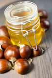 Jar of honey with organic chestnuts on a wooden table Royalty Free Stock Images