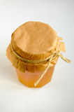 Jar of honey with a paper cover tied with a rope. On a table Royalty Free Stock Images