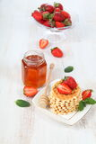 Jar of honey, ripe strawberries and waffles Royalty Free Stock Image