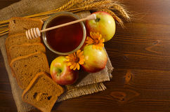 Jar with honey, rye bread, apples, yellow daisy and ears on sacking, wooden table Stock Photography