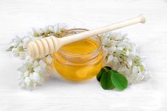 Jar with honey and acacia flowers on a white wooden background royalty free stock image