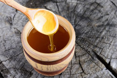 Jar of honey and spoon with honey on a wooden background Royalty Free Stock Photo