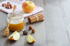 Jar of honey, honey stick, cinnamon, hazelnuts and red apple Stock Photo