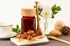 Jar of honey on a table with wild flowers and desserts. Jar of honey on a table with wild flowers and other ingredients royalty free stock image