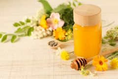 Jar of honey on a table with wild flowers. And other ingredients stock photo