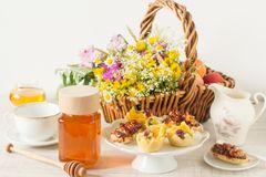 Jar of honey on a table with wild flowers and desserts. Jar of honey on a table with wild flowers and other ingredients royalty free stock images