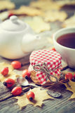 Jar of honey, tea cup and teapot on background. Maple leaves and dog rose berries on wooden table. Autumn still life. Selective focus Royalty Free Stock Photography