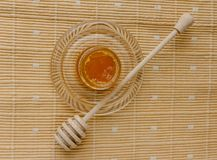 Jar of honey on a textile tablecloth. Glass saucer and wooden spoon, kitchen utilities. Home made organic mask ingredients. Healthy eco lifestyle. Food blog Royalty Free Stock Image