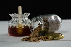 Jar of honey and wheat flakes spilling out of bottle Stock Images