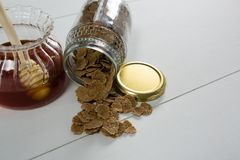 Jar of honey and wheat flakes spilling out of bottle Stock Image