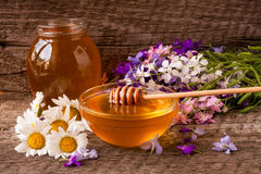 Jar of honey with wildflowers and chamomile on old wooden background Royalty Free Stock Photography
