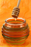 Jar of honey with wood stick Royalty Free Stock Image