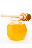 Jar of honey with wood stick Stock Image