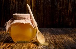 Jar of honey on a wooden background Stock Photography
