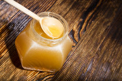 Jar of honey on a wooden background Royalty Free Stock Images