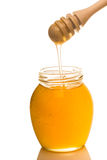 Jar of honey with wooden drizzler isolated on white background Royalty Free Stock Photo