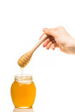 Jar of honey with wooden drizzler isolated on white background Stock Images
