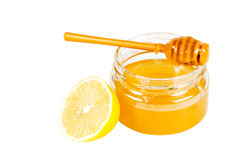 Jar of honey with a wooden drizzler and a lemon. Royalty Free Stock Photography