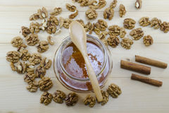 Jar of honey, wooden spoon and wallnuts Stock Image