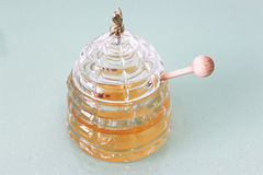 Jar with honey and wooden stick Royalty Free Stock Photography