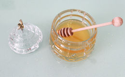 Jar with honey and wooden stick, cover with bee Royalty Free Stock Photo