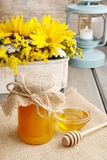 Jar of honey on wooden table, bouquet of sunflowers in the backg Royalty Free Stock Image