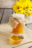 Jar of honey on wooden table, bouquet of sunflowers in the backg Royalty Free Stock Images
