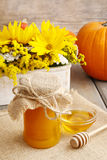 Jar of honey on wooden table, bouquet of sunflowers in the backg Stock Photos