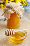Jar of honey on wooden table, bouquet of sunflowers in the backg Royalty Free Stock Photos