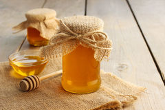 Jar of honey on wooden table Stock Photos
