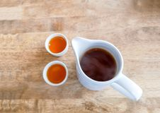 A jar of hot tea and two cups on brown wooden table for drinking time, top view image. A jar of hot tea and two cups on brown wooden table for drinking time stock images