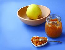 Jar of jam and apple. Jar with a jam from a apple on a indigo table Royalty Free Stock Photography