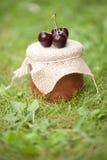 Jar of jam with cherries. One jar of jam and cherries Royalty Free Stock Image